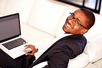 Portrait of handsome African American business man using laptop while looking at you
