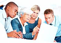 Female mature leader with multi ethnic colleagues pointing at laptop during meeting