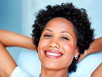 Closeup portrait of beautiful African American woman relaxing with hands behind head