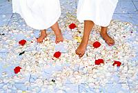 Feet standing amongst flower petals