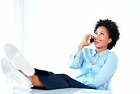 Smiling African American female executive using cellphone with legs on desk