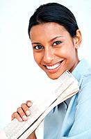 Closeup of young female executive smiling holding newspaper over white background