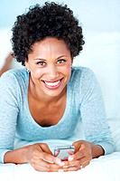 Portrait of lovely African American woman smiling while reading text message on couch