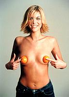 Blond young woman holdin two oranges on her breast