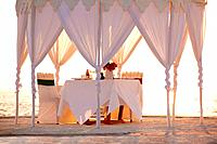 Image of a beautiful restaurant tent with table served on the beach