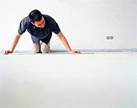 Man measuring floor in room
