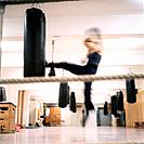 Female kickboxer kicking punchbag