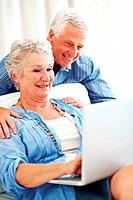 Portrait of a happy senior woman using laptop with her husband