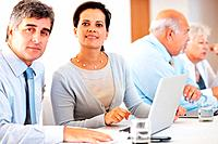 Mature business associates with laptop with senior couple in the background