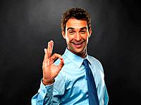 Portrait of smiling business man giving you OK sign on black background
