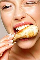 Young woman eating chicken leg