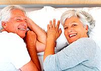 Closeup portrait of senior couple lying on bed and giving you an attractive smile