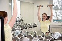 woman training in a fitness studio with dumbbells