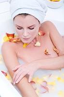 pretty woman taking a wellness bath with petals