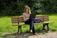 business woman sitting on a park bench working at the laptop on her knees