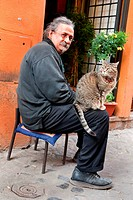man with a cat on his lap sitting in an alley of Trastevere, Italy, Trastevere, Rome