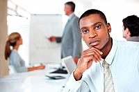 Portrait of confident young businessman sitting in a meeting at office