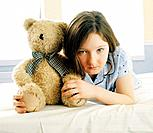 Girl on hospital bed holding teddy bear