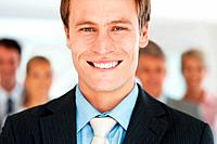 Closeup portrait of a happy young businessman smiling and his team in background