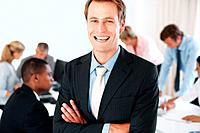 Smart young businessman laughing with his hands folded and his colleagues working behind at office