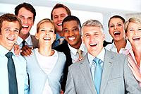 Group of a successful business people standing together at office and smiling