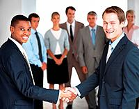 Happy business people greeting each other at office with team standing in background