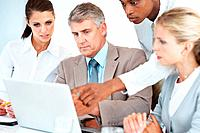 Confident man discussing a project with colleagues pointing at laptop