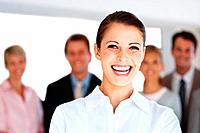 Portrait of a smart young businesswoman smiling with her colleagues standing behind at office