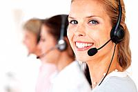 Closeup portrait of a happy young call center employee wearing headset with her colleagues in background