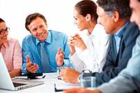 Smiling mature business man explaining project to his colleagues during meeting