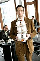 Office Worker Carrying a Pile of Coffee Beakers in Office