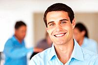 Closeup portrait of happy business man smiling with colleagues in background