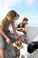 Group of Teenagers and Dog with Popsicles at Wall