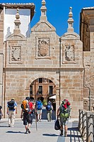 pilgrims in front of town gate, Spain, Basque country, Navarra, Los Arcos