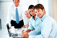 Portrait of smart young businessman sitting a a presentation with colleages