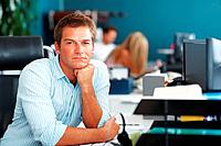 Businessman sitting at desk deep in thought with colleagues blur in background