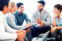 Smiling business people listening to their leader during meeting