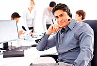 Confident customer executive sitting in front of computer with colleagues in background