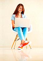 Full length of pretty young girl sitting on chair using laptop and smiling