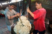 Two men with paddles mix popped rice and sugar to make rice candy Mekong Delta Vietnam