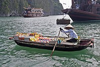 Woman rows floating supply boat with biscuits drinks cooking oil and cakes among tourist cruising boats Halong Bay Vietnam