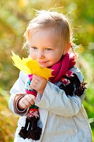 little girl collecting autumn leaves