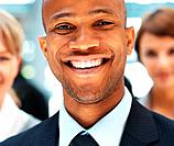 Closeup of businessman smiling with colleagues in background