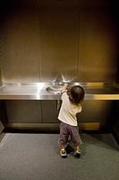 A small child trying to get a drink of water at a water fountain