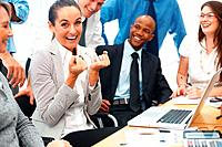 Excited business woman clenching her fists with colleagues look on