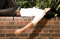 Young Man with Headphones Lying on Wall