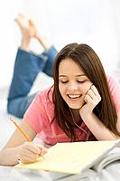 Female teenager wearing headphones writing