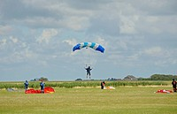 sky divers landing in a meadow, Netherlands, Northern Netherlands, Netherlands, Texel