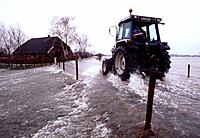 Tractor Driving over Flooded Road