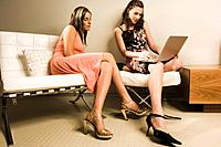 Two Young Women Sitting on Sofa Using Laptop